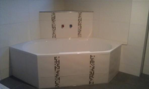 weiße Badewanne mit Mosaikstreifen