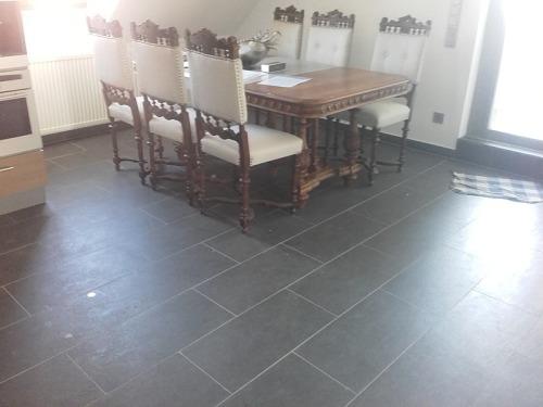Küche mit Esstisch auf dunklen Fliesen