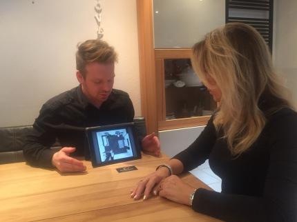 Fliesenleger Tino Klug erklärt Frau die 3D-Badplanung