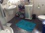 kleines Bad mit weißen Fliesen und grauem Boden